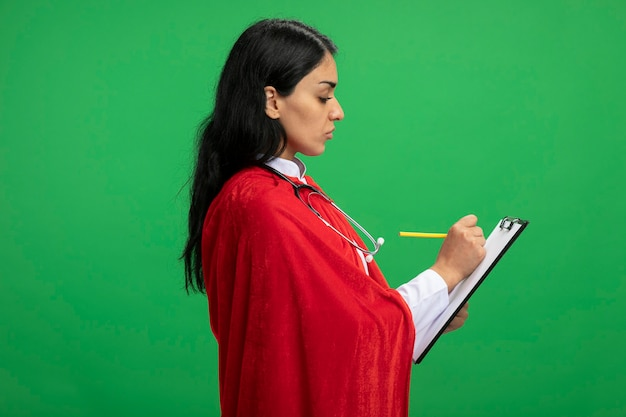 Standing in profile view young superhero girl wearing medical robe with stethoscope holding and writing something on clipboard isolated on green