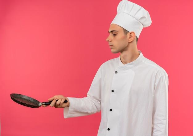 In piedi nel profilo giovane cuoco maschio indossando chef uniforme holding e cercando padella con spazio di copia