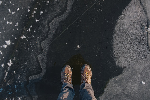 Standing on the thin ice, top view. human feet on beautiful textured ice on the lake or river