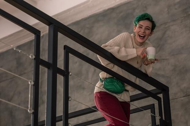 2 階に立っています。 2階に立っている家族に話しかけながら笑う緑髪の女性