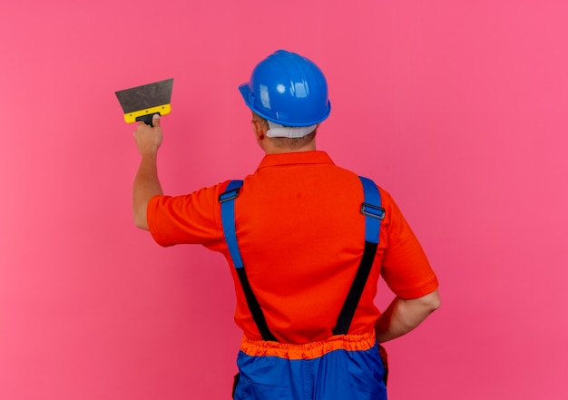 Standing in behind view young male builder wearing uniform and safety helmet holding putty knife