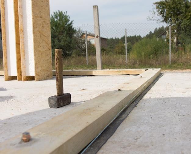 Стоящий старинный молоток плотника на строительной площадке с предварительно установленным прочным деревянным фундаментом.