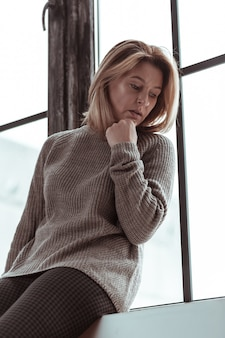 Standing and waiting. blonde-haired woman standing near the window and waiting for husband from work