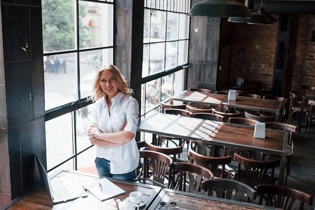 腕を組んで立っている。昼間のカフェで室内に金髪の巻き毛を持つ実業家。