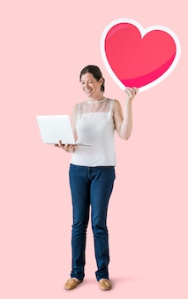 Standing woman holding a heart emoticon and a laptop