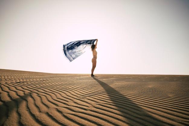 Стоящая женщина в бикини на пляже наслаждается летними каникулами, играя с ветром в одиночестве