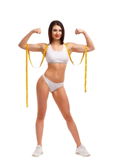 Standing woman squeezing both biceps and a tape measure