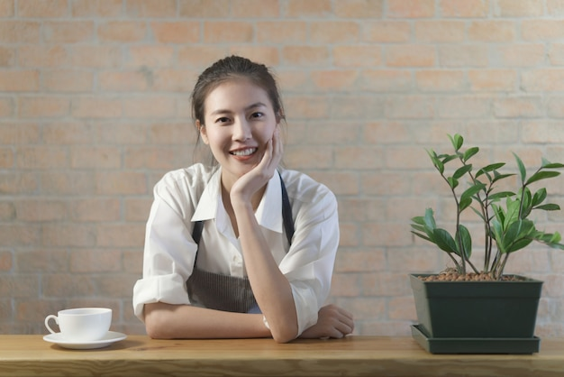 Standing young cute asian coffee barista girl is relaxing on the table bar