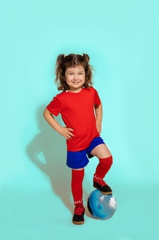 Standing young soccer player girl 5-6 years holding football with foot