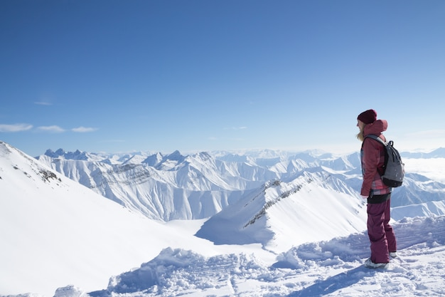 Standing young woman with backpack on the mountain peak against beautiful mountains and glacier
