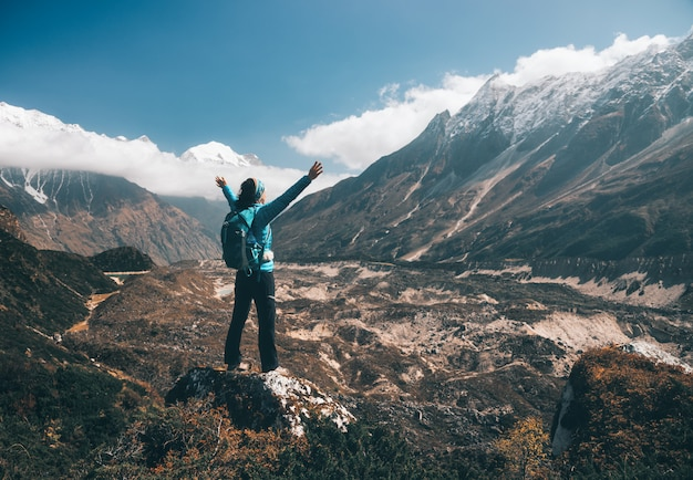 Standing young woman with backpack and raised up arms on the hill and looking on mountains