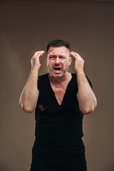 傷のある黒いtシャツにボロボロの怒っている男が立っています