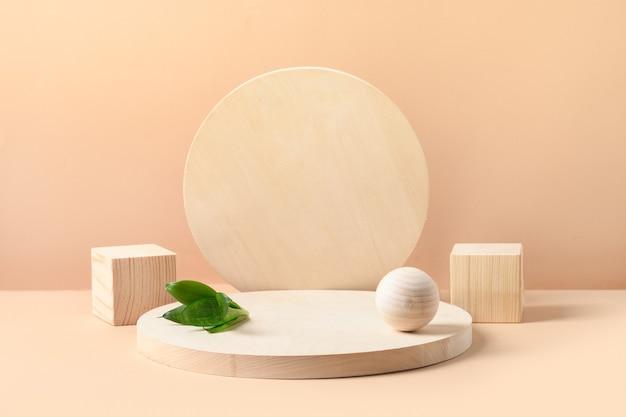 Подставки для изделий из дерева натуральных форм. куб, шар и тарелка как подиум. творческая композиция с зелеными листьями на бежевом фоне.