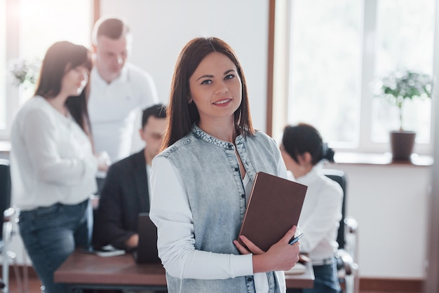 Stands in front of her colleagues. group of people at business conference in modern classroom at daytime