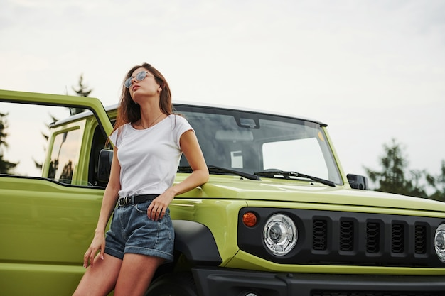 Stands near new vehicle. pretty woman in the green modern car posing for the camera.