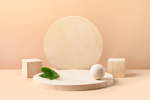 Stands for product of wooden natural shapes. cube, ball and plate as podium. creative composition with green leaf on beige background.