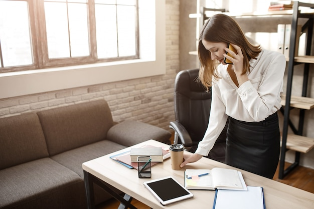 Занятая молодая женщина stantd за столом в комнате. она разговаривает по телефону и пишет в тетради.