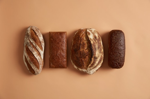 Staple food and healthy nutrition concept. four types of bread isolated on brown background. wheat, rye, spelt bread enriched with vitamins and minerals, made of organic flour, has health benefits