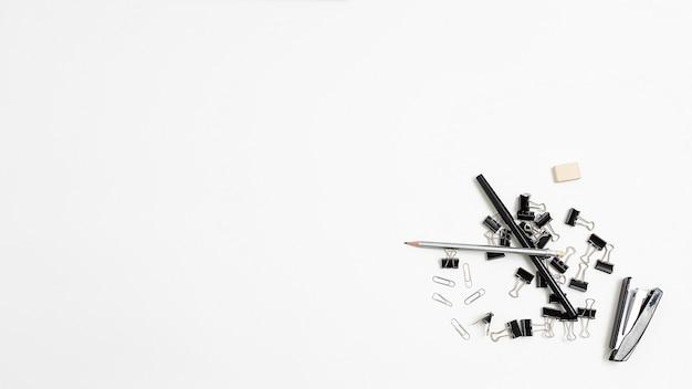 Степлер, ластик, связка черных металлических скрепок для документов, карандаши, случайно разбросанные в кучу на белом фоне