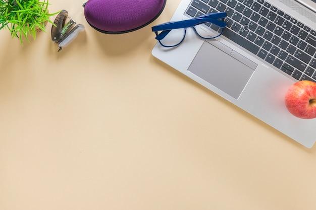 Stapler; eyeglasses and apple on laptop over the beige background