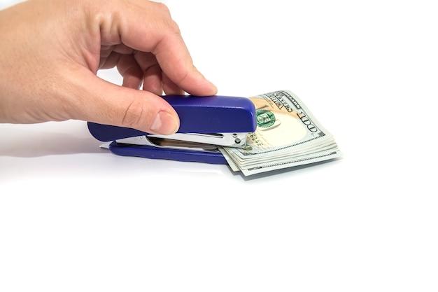 스테이플러는 고립 된 달러를 뚫습니다. 손은 스테이플러로 돈을 펀칭합니다.