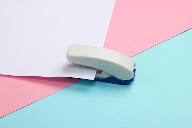 Степлер протыкает белый лист бумаги на сине-розовой пастели.