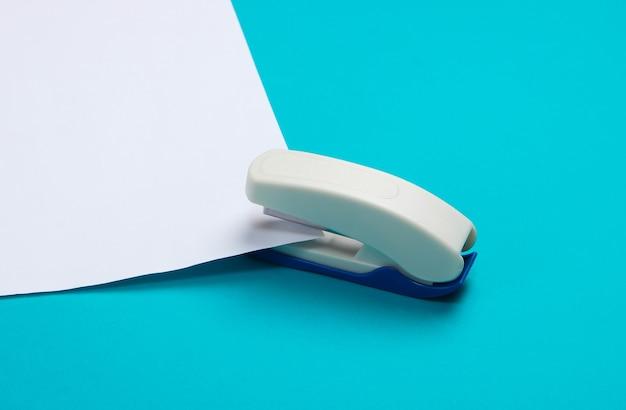 Степлер протыкает белый лист бумаги по синему.