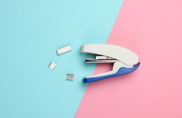Stapler with paper clips on a blue-pink pastel.