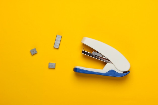 Stapler with paper clips on yellow.