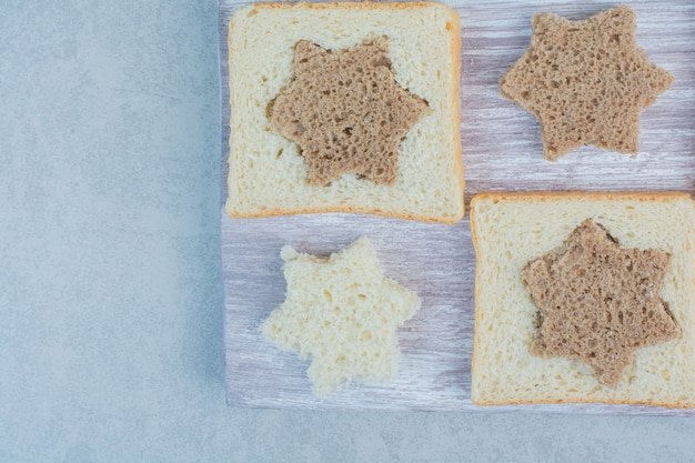 大理石の背景に星と正方形の形をした黒と白のパンのスライス。高品質の写真