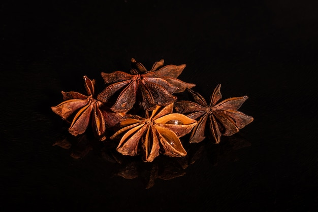 Star anise against a dark background. spice on a glass background with reflection