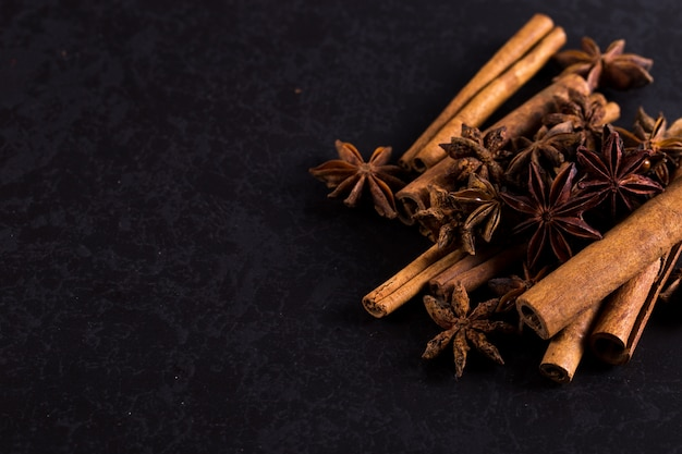 Star anise and cinnamon on a black table. , copyspace.