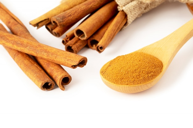 Star anise, cinnamon sticks and powder in wooden spoon isolated