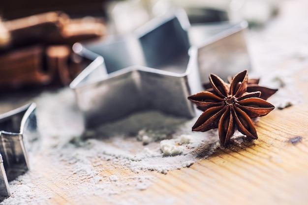 ベーキングボード上のスターアニスクッキーカッターシナモンと小麦粉クリスマスのベーキングと休日のコンセプト