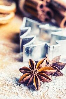 ベーキングボード上のスターアニスクッキーカッターシナモンと小麦粉クリスマスベーキングlと休日のコンセプト