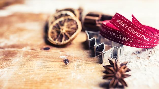 ベーキングボードにテキストメリークリスマスとスターアニスクッキーカッターシナモン小麦粉赤いリボン。