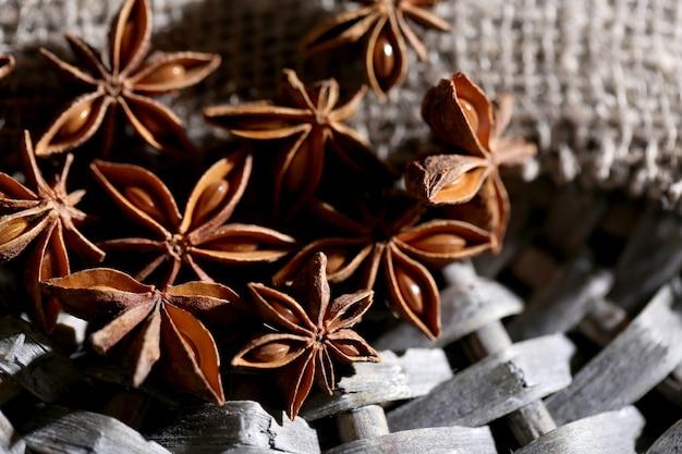 Звездчатый анис на плетеной циновке, на деревянных фоне