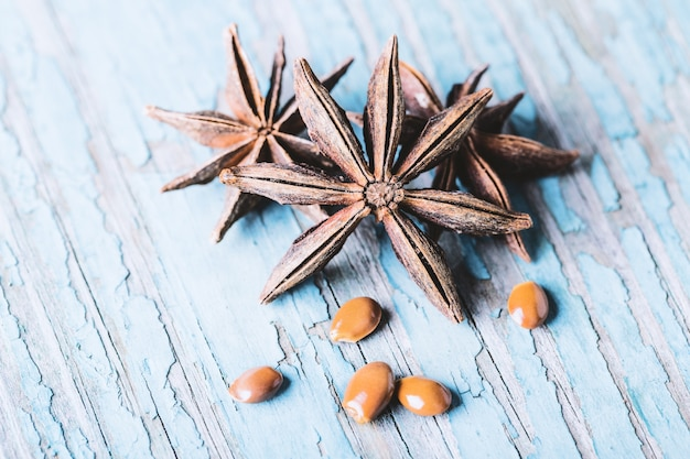 Star anise with seeds on old wooden background close-up with copyspace.