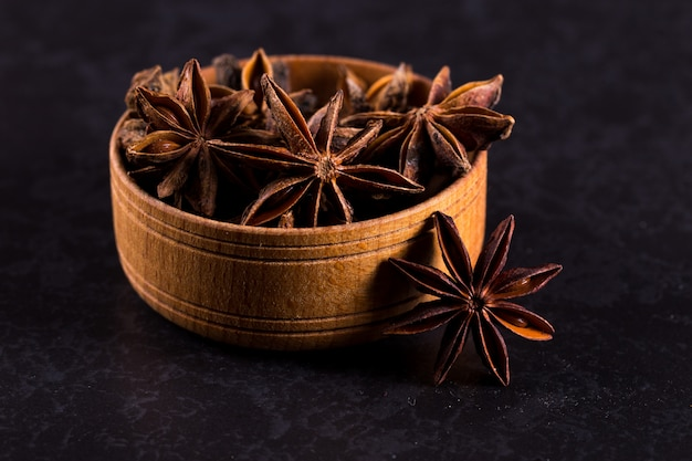 Star anise in a wooden bowl on a black table. , copyspace.