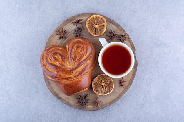 Звездчатый анис, сушеные дольки лимона, чашка чая и сладкая булочка на деревянной доске на мраморной поверхности