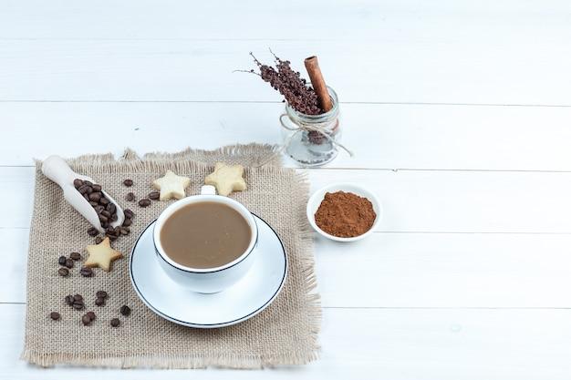 Звездное печенье, кофейные зерна, чашка кофе на куске мешка с миской растворимого кофе, банка трав под высоким углом обзора на фоне белой деревянной доски