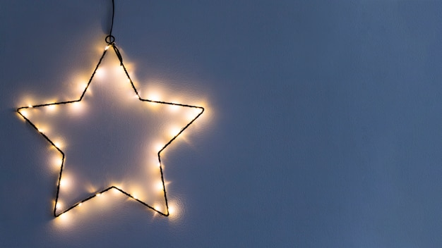 Star made from burning garland on wall