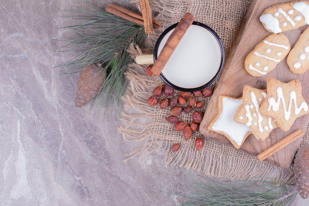Biscotti di panpepato stella e ovale su una tavola di legno con cannella e una tazza di latte