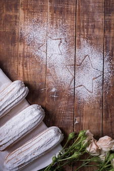 Star shape drawn on wooden desk with baked eclairs and roses