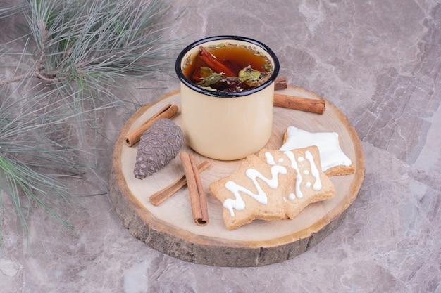 Biscotti di panpepato a forma di stella con una tazza di tisana e cannella.