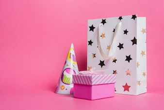 Star shape shopping bag; paper hat and gift box on pink background