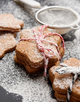 Star shaped baked gingerbread cookies sprinkled with powdered sugar on a black table, close up