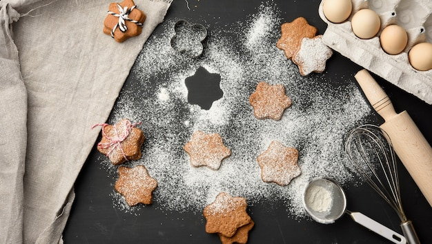 Star shaped baked gingerbread cookies sprinkled with powdered sugar on a black table, top view