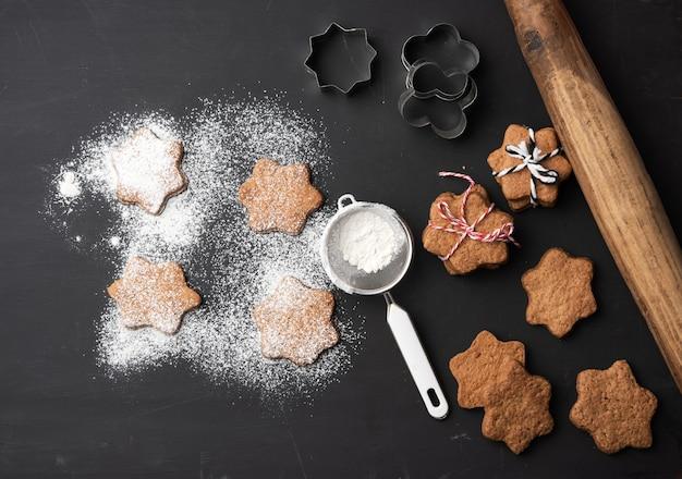 Запеченные имбирные пряники в форме звезды, посыпанные сахарной пудрой, на черном столе, вид сверху