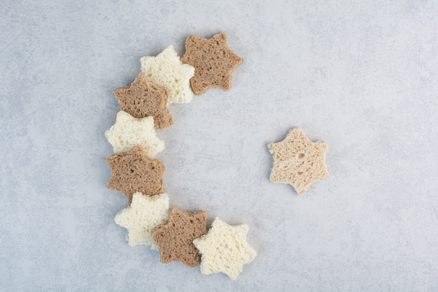 Ломтики черного и белого хлеба в форме звезды на мраморном фоне. фото высокого качества